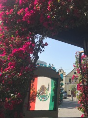 Overlooking: a little chapel behind the beautiful mexican flag surrounded by bugambilias. (Bougainvillea flower)